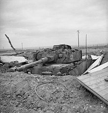A frontal view of a knocked out German tank in a hull-down position, protected by earth entrenchments.