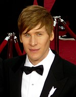 Profile of a man with medium brown hair at a red carpet event. He is seen wearing a white collared shirt and black tuxedo accented with a black bowtie.