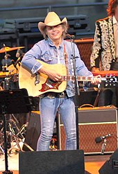 A man in a cowboy hat, denim jacket and blue jeans playing a guitar on stage