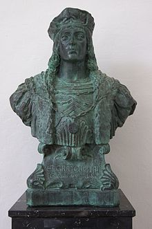 Bronze bust of man with long hair and a hat