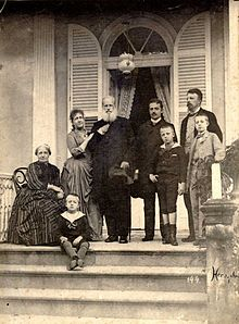 Photograph of a group of people assembled on a columned porch at the top of a flight of steps, with one older lady seated, one younger lady leaning on the arm of an older bearded man, two younger men and three small boys