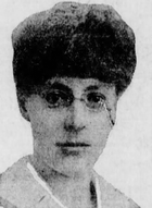 Headshot of a woman wearing a fur hat and eyeglasses