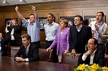 Prime Minister David Cameron of the United Kingdom, President Barack Obama, Chancellor Angela Merkel of Germany, José Manuel Barroso, President of the European Commission, President François Hollande of France and others react emotionally while watching the overtime shootout of the Chelsea vs. Bayern Munich Champions League final, in the Laurel Cabin conference room during the G8 Summit at Camp David, Maryland, May 19, 2012. Cameron raises his arms triumphantly as the Chelsea team wins air first Champions League title in the overtime shootout.