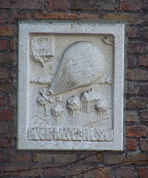 "Relief celebrating the first post delivery by a hot airballoon, landing in the Netherlands in 1870 (the French ""L'Archimède"" from Paris to Castelre by accident) at the backside of the Town Hall of Baarle-Nassau."