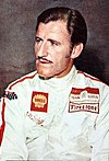 Graham Hill in a racing suit looking to the right of the camera