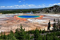 Pool of blue water surrounded by orange and yellow residue, in ashen rock basin.