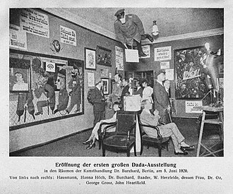 Dada - Grand opening of the first Dada exhibition: International Dada Fair, Berlin, 5 June 1920. The central figure hanging from the ceiling was an effigy of a German officer with a pig's head. From left to right: Raoul Hausmann, Hannah Höch (sitting), Otto Burchard, Johannes Baader, Wieland Herzfelde, Margarete Herzfelde, Dr. Oz (Otto Schmalhausen), George Grosz and John Heartfield.