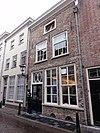 foto van Huis met eenvoudige grijsgepleisterde lijstgevel, bovenvensters met kleine witte roedenverdeling