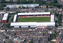 A white roofed football stadium with red seats seen from the air. It is surrounded by residential housing