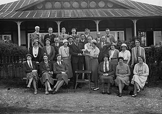 Group outside Llandrindod Wells Golf Club pavilion, with a lady golfer being presented with a cup