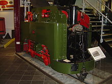 A small green tank steam locomotive of unusual design, number 13, stands in the museum. The power to the wheels comes from a crank-shaft at the upper rear of the locomotive, which is transmitted to the rear wheel via a vertical connecting rod on the right hand side. The rear wheels are connected to the front wheels by a conventional horizontal connecting rod. A plaque on the front of the locomotive reads WILLIAM SPENCE S. GEOCHECANS PATENT, with a final line obscured by a hand rail rising from the front buffer beam.