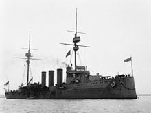 A large dark gray warship sits motionless in the water; it has four tall, thin smoke stacks closely arranged in the middle of the ship with two tall masts on either end.