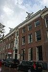 foto van Statig patriciershuis, met rechte kroonlijst en gebeeldhouwde middenpartij, stoep, deur met bovenlicht met takken en trossen, hek met fraai régence smeedwerk