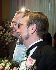Joyful-looking male couple holding a wedding bouquet