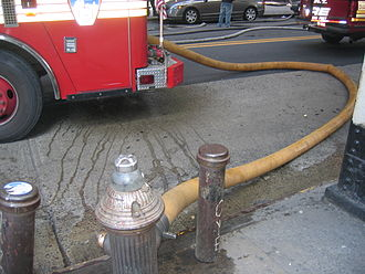 Fire hydrant - A New York City hydrant hooked to an FDNY fire engine with a turgid hose actively pumping water.