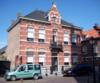 foto van Herenhuis, gebouwd in eclectische stijl met natuurstenen stoep, stoeppalen en ten zuiden aan de voorgevel een ijzeren hekwerk tussen rode bakstenen kolommen