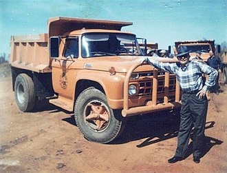 Louisiana Department of Transportation and Development - A Louisiana Highway Department gravel truck driver pauses in front of his orange-colored vehicle (1972).