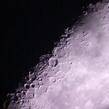 Lunar craters as captured through the backyard telescope of an amateur astronomer, partially illuminated by the sun on a waning crescent moon.
