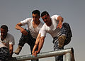 Members of Iraqi Police and Border Patrol climb over the monkey bars while running an obstacle course at the Police Academy in Basrah, Iraq, May 4, 2011 110504-A-YD132-177.jpg