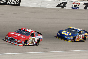Ken Schrader and Michael Waltrip racing in a 2006 NASCAR Nextel Cup Series practice session at Texas Motor Speedway.