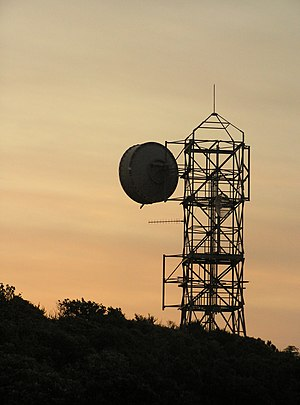 Microwave telecommunications tower, silhouette...