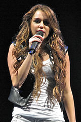 A brunette teenager sings into a microphone. She is wearing a black leather vest over a white tank top and shorts.