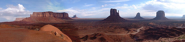 Panorama of rock formations at Monument Valley in Arizona.  A red, barren, desert landscape with several mesas and gigantic, unusual rock formations.