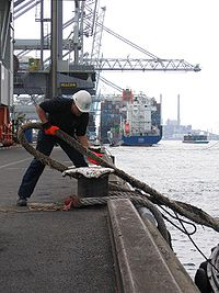 A dockworker places a mooring line on a bollard.