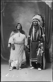 Photographic portrait of Pohene and Frank George, two Shoshone people in traditional dress