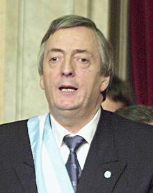 Kirchner speaking, wearing a ceremonial sash