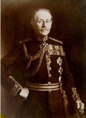 Portrait d'un officier de l'armée britannique en uniforme avec aiguillettes et médailles de service, face à l'avant avec une main sur la hanche