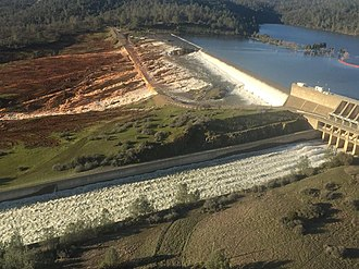 Oroville Dam - Water overflows the parking lot past the emergency spillway (in the background), while water continues to flow through the main spillway (in the foreground), on February 11.