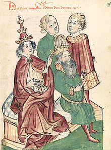 A young man wearing tiara touches the head of a bearded man sitting on his side, with two men watching the scene.