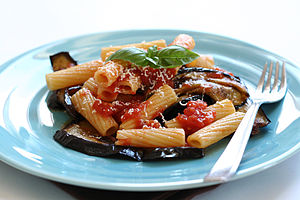 A plate of pasta with tomatoes, eggplant, basil, and cheese
