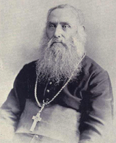A bearded elderly man wearing a pectoral cross around his neck faces towards the left.