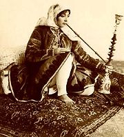 Femme iranienne, en robe Qajare, en train de fumer le Ghelyan traditionnel.