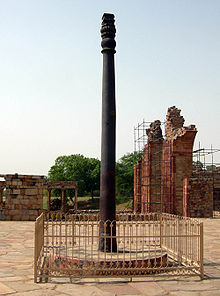 An pillar, slightly fluted, with some ornamentation at its top. It is black, slightly weathered to a dark brown near the base, it is around 7 meters (23 feet) tall. It stands upon a raised circular base of stone, and is surrounded by a short, square fence.
