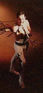Un homme vu de face et en plongée, torse nu, vêtu d'un pantalon noir et blanc. Il grimace et lève sa main droite, tout en tenant un pied de micro dans sa main gauche.