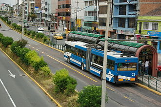 "Trolleybuses in Quito - A trolleybus stopped at the ""Estadio"" station, in the trolleybus-only lanes in of Avenida 10 de Agosto."
