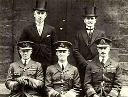 Portrait of five men, three seated wearing dark military uniforms with peaked caps, and two standing behind wearing formal suits with top hats
