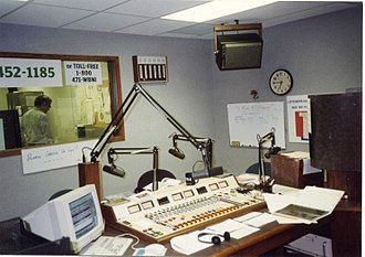 Radio producer - In this studio from radio station WBNI, the producer sits in the foreground and operates the mixing console, while the on-air performers sit across the table and speak into the microphones.