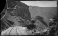 Railway line curving around a bend, across a narrow gully, towards a tunnel ATLIB 312799.png