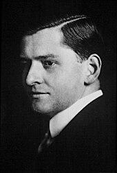 Czarno-biały portret mężczyzny w garniturze i pod krawatem.  Połowa jego twarzy jest w cieniu.