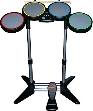 Rock Band (video game) - The drum controller, which features 4 pads, a bass drum pedal, and real drumsticks.