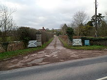 A road entrance to a building consisting of white-painted wooden gates, facebrick walling in a green landscape which prominently features various tree species.
