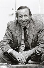 Roy E. Disney sitting in a suit and grinning