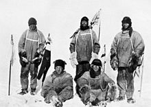 Five men(three standing, two sitting on the icy ground) in heavy polar clothing. All look exhausted and unhappy. The standing men are carrying flagstaffs and a Union flag flies from a mast in the background. Scott's party at the South Pole.  Left to right: Oates; Bowers; Scott; Wilson; Evans