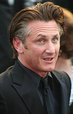 A man wearing a black suit including a black shirt and tie.