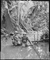 Sergeant Carl Weinke and Private First Class Ernest Marjoram, Signal Corps cameramen, wading through stream while... - NARA - 531186.tif