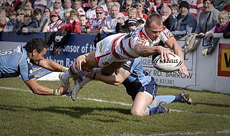 Try - Shaun Ainscough dives for the line to score a try in the 2009 Challenge Cup for Wigan during their victory over Barrow Raiders